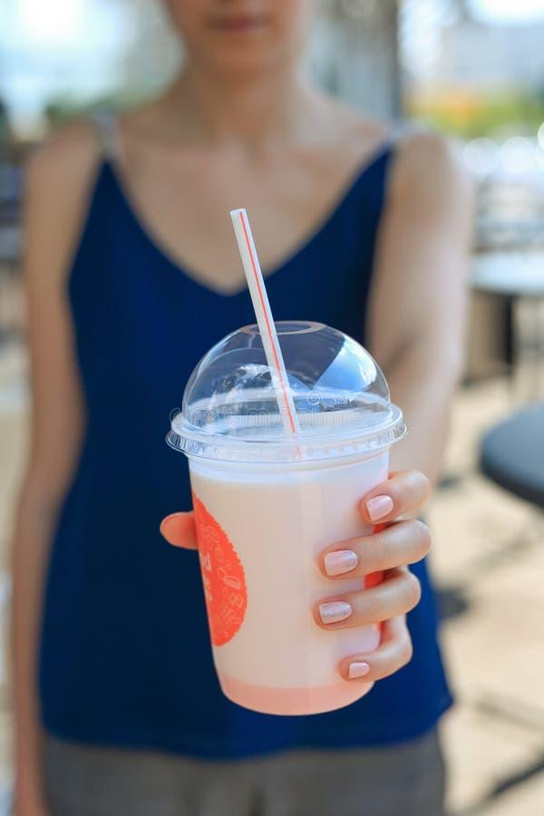 享用桃红色圆滑的人的妇女 拿着在一块玻璃的少女奶昔与在一个咖啡馆的秸杆外面在夏天 免版税库存图片
