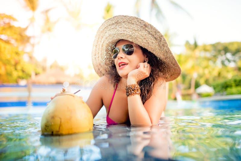 享用椰子鸡尾酒的妇女在水池酒吧,当有好时光在水中时 免版税库存图片