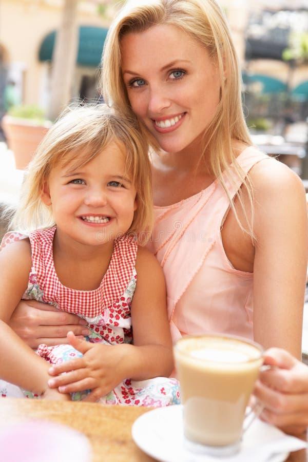 享用母亲的咖啡杯女儿 图库摄影