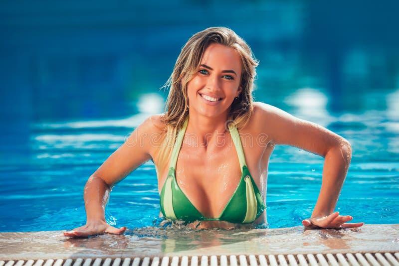 享用比基尼泳装的晒黑妇女在游泳池 库存图片