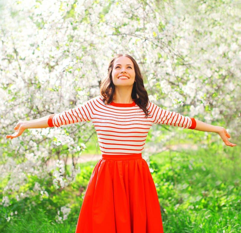 享用气味的愉快的俏丽的微笑的妇女开花在春天 库存照片