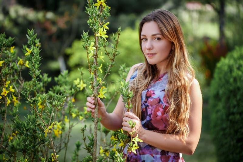 享用气味的画象美丽的愉快的妇女在一个开花的春天开花的庭院里 在blos附近的聪慧和时兴的微笑的女孩 免版税图库摄影
