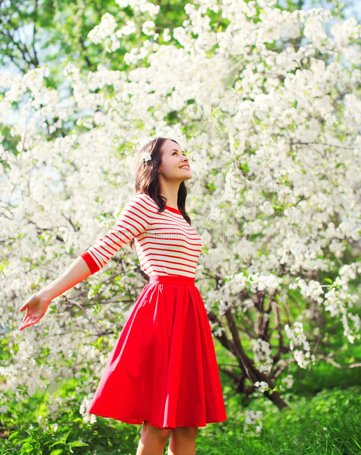 享用气味的美丽的愉快的少妇在开花的春天庭院里 库存图片