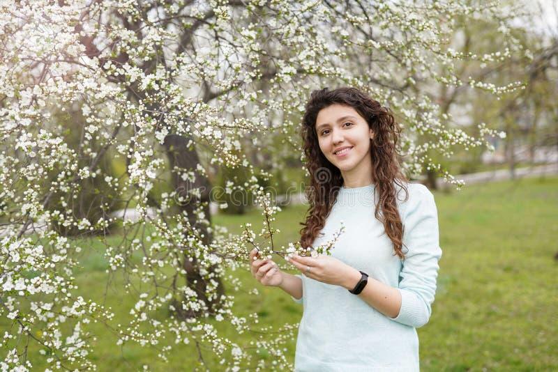 享用气味的美丽的愉快的年轻女人在一个开花的春天庭院里 免版税库存照片