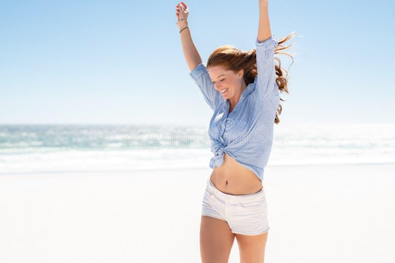 享用海滩的微笑的妇女 免版税库存照片