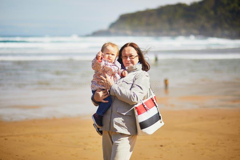 享用海滩的祖母和孙女大西洋 免版税库存照片