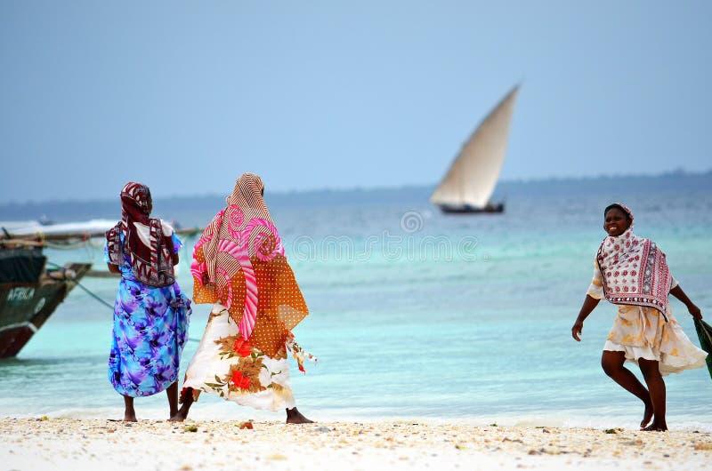 享用海滩,桑给巴尔的回教妇女 免版税图库摄影
