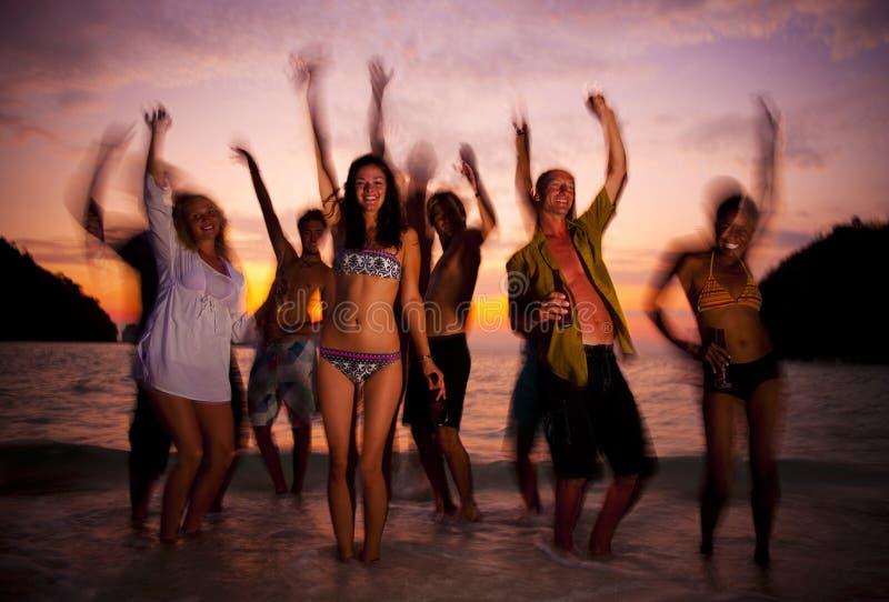 享用海滩的大小组青年人集会 免版税库存图片