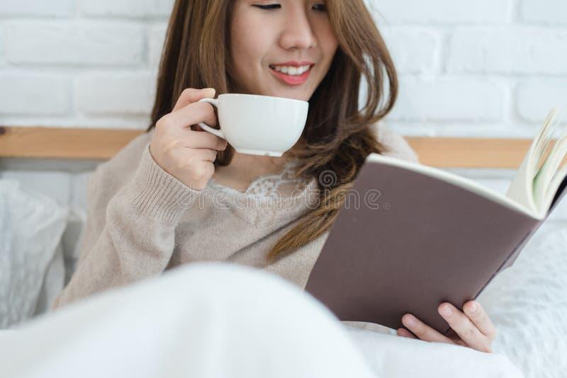 享用温暖的咖啡和阅读书在床上的美丽的亚裔妇女在她的卧室 免版税库存图片