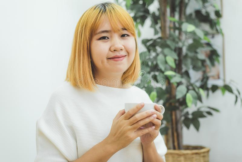享用温暖的咖啡的可爱的美丽的亚裔妇女在厨房里在她的家 免版税库存图片