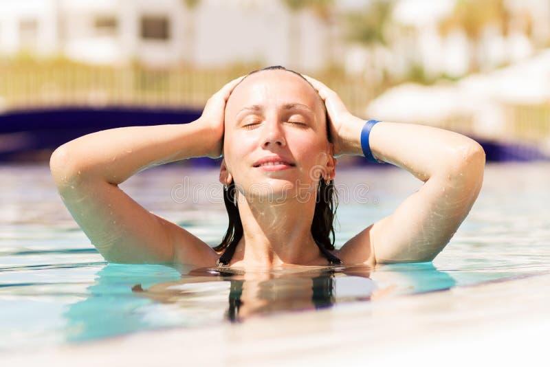 享用游泳池的少妇热带暑假 库存图片