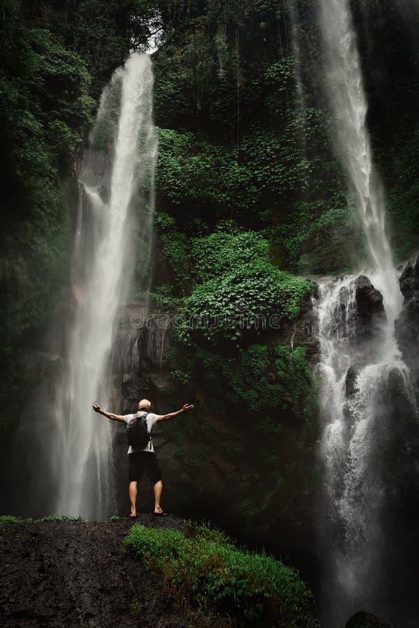 享用瀑布的人举了手 旅行生活方式和成功概念假期到在背景的狂放的自然里 免版税库存照片