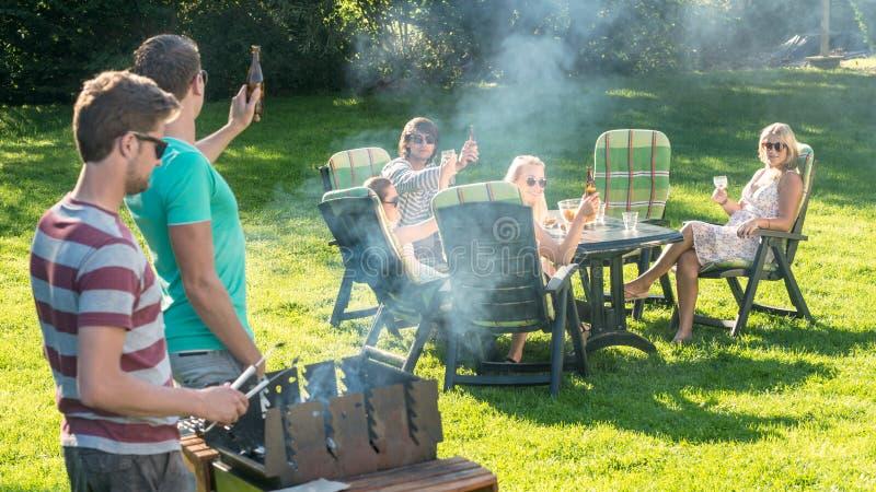 享用烤肉的朋友在庭院里 免版税库存照片
