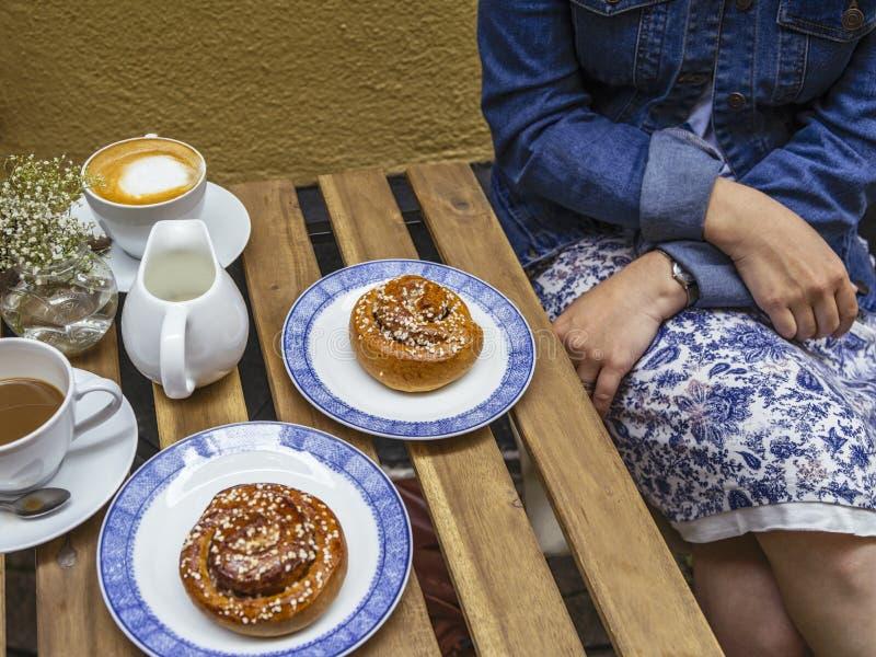 享用瑞典酥皮点心Kanelbulle和咖啡 免版税库存照片