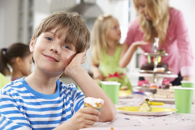 享用生日聚会食物的小组孩子在表上 库存照片