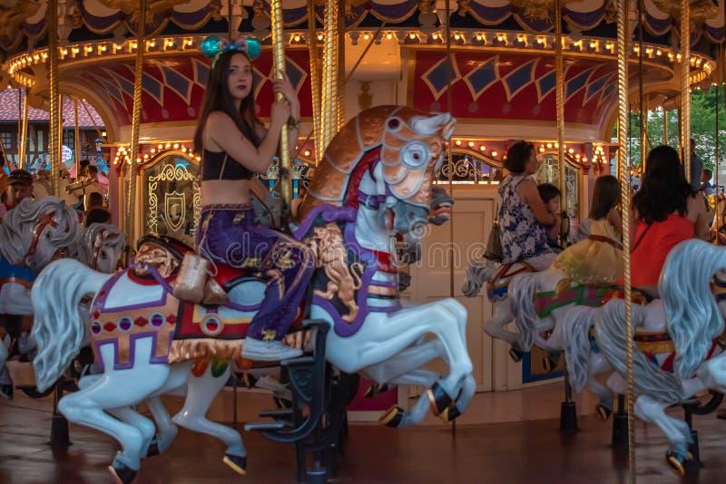 享用白马王子豪华转盘的妇女在不可思议的王国在华特・迪士尼世界 免版税库存照片