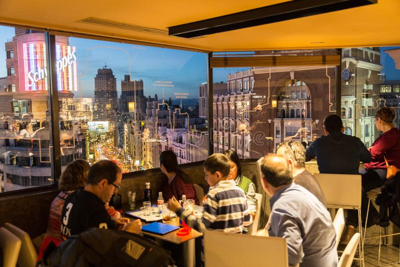 享用的人们平衡饮料和使马德里惊奇全景在El Corte英格尔斯屋顶酒吧的黄昏  库存照片