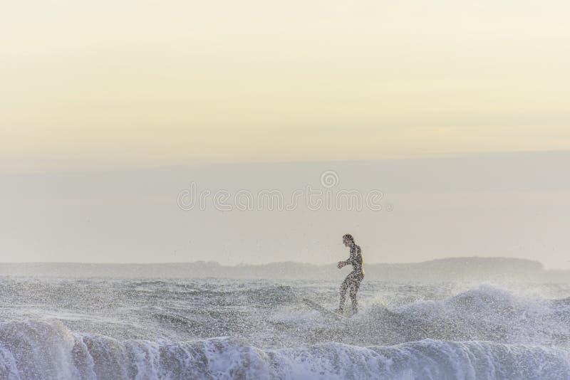 享用的冲浪者平衡海浪在风大浪急的海面在得到的日落飞溅由水 库存照片