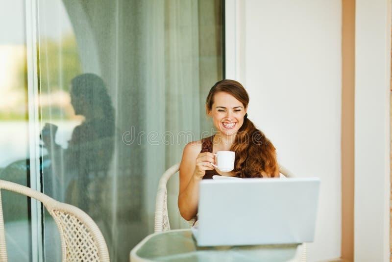 享用的咖啡杯笑妇女年轻人 库存图片