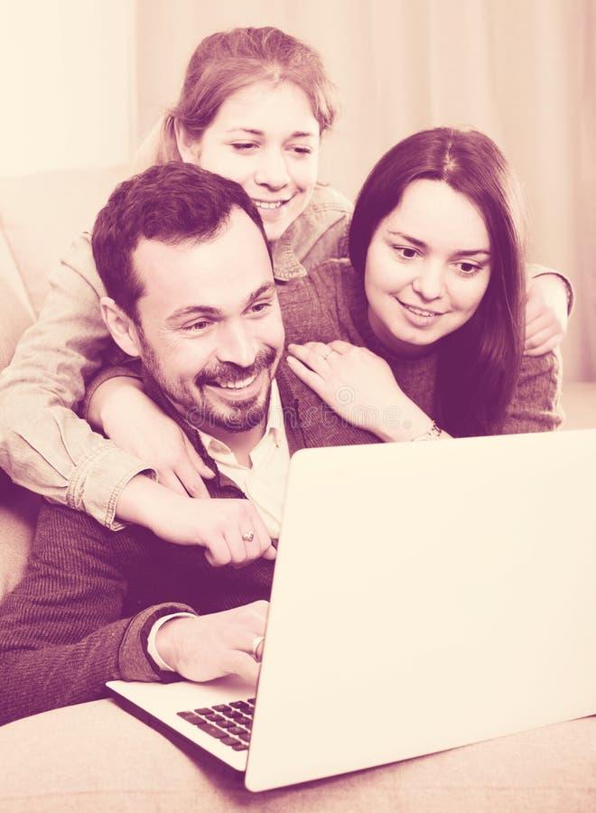 享用的家庭成员预定旅馆一起在网上膝上型计算机的 免版税库存图片