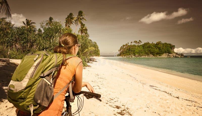 享用的少妇站立与在沿海的自行车和是 免版税图库摄影