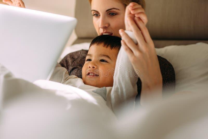 享用的母亲和的儿子观看在膝上型计算机的动画片电影 免版税库存照片