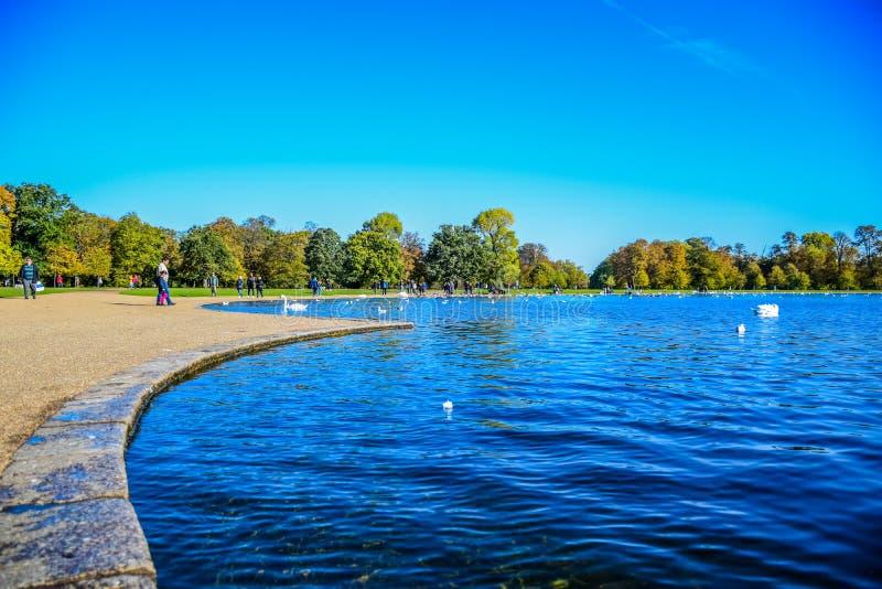 享用的游人花费和他们在圆的池塘放松时间在肯辛顿宫前面的肯辛顿庭院里在伦敦,英国 库存照片
