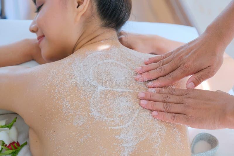 享用盐的亚洲美女洗刷按摩在健康温泉在泰国 库存照片
