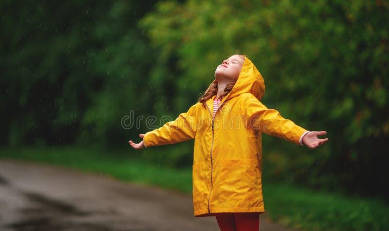 享用秋天雨的愉快的儿童女孩 免版税库存图片