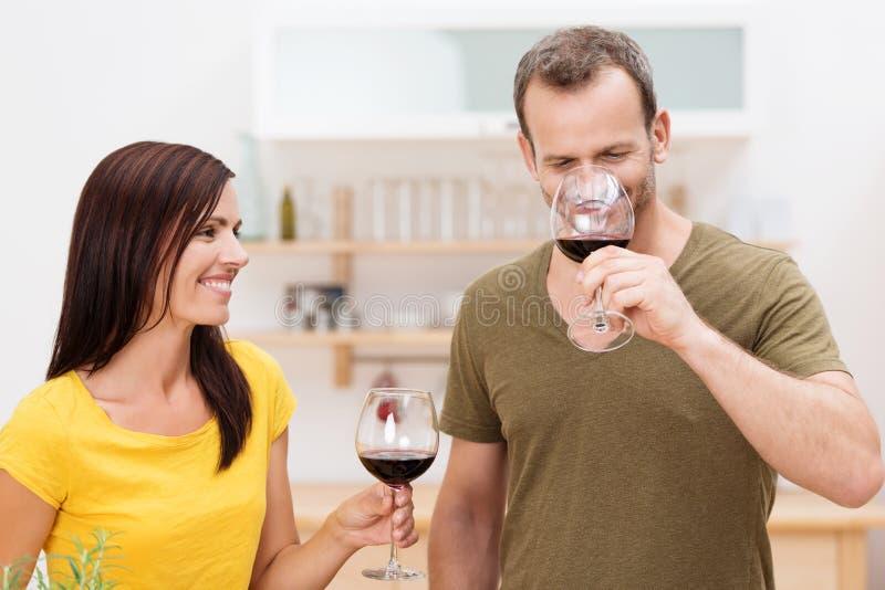 享用红葡萄酒的微笑的夫妇在厨房里 免版税库存图片
