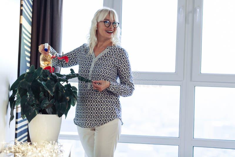享用绿色植物的快乐的好白肤金发的妇女 免版税库存照片