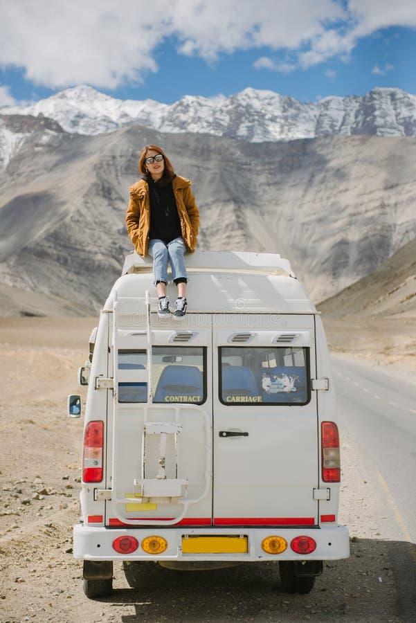 享用美丽的山的年轻亚裔女孩坐汽车屋顶 免版税库存照片