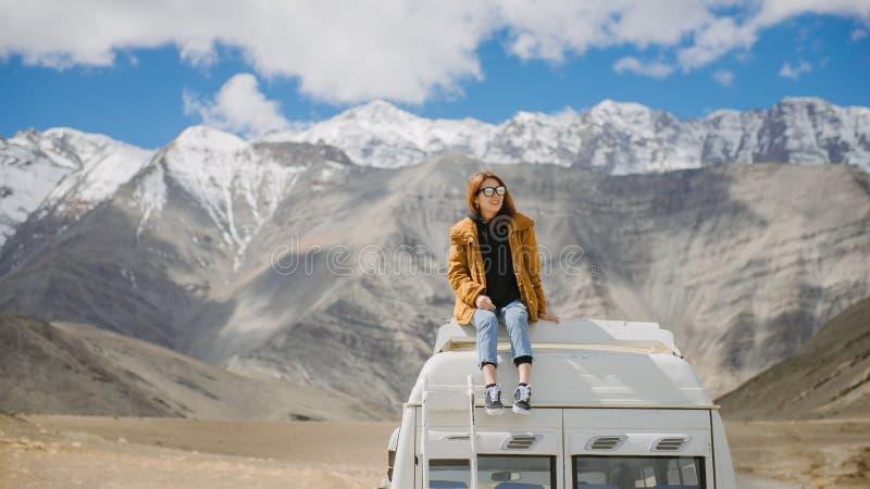 享用美丽的山的年轻亚裔女孩坐汽车屋顶 库存图片