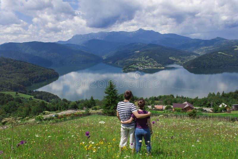 享用美丽的湖和山的男人和妇女夫妇  免版税库存照片