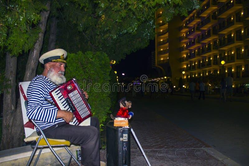 享用老的人演奏手风琴 图库摄影