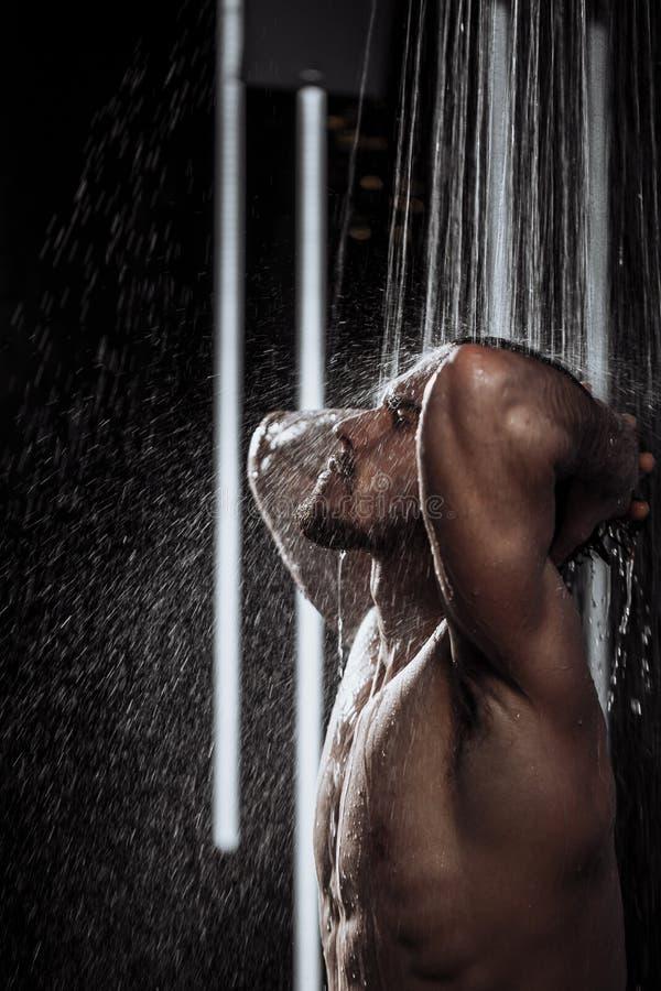 享用肌肉的人用被举的手有对比阵雨 库存照片