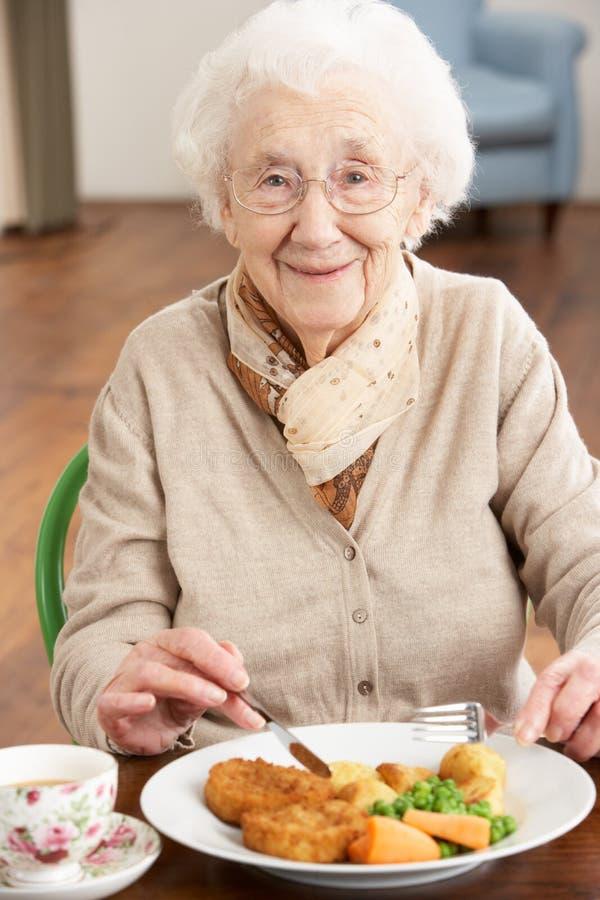 享用膳食前辈妇女 免版税库存照片