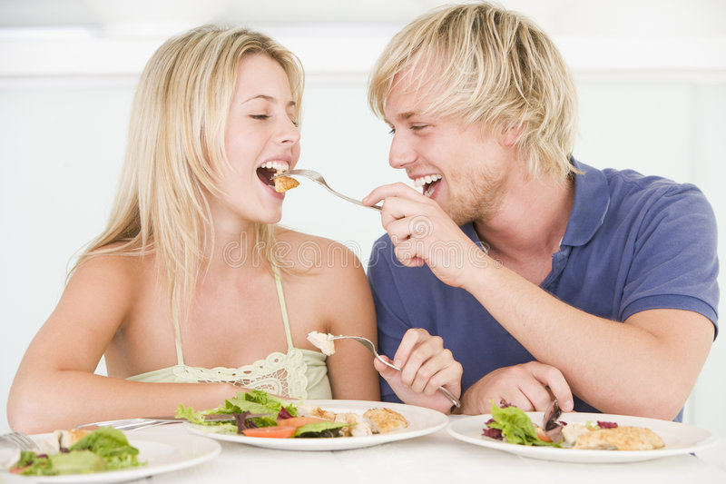 享用膳食年轻人的夫妇 免版税库存照片