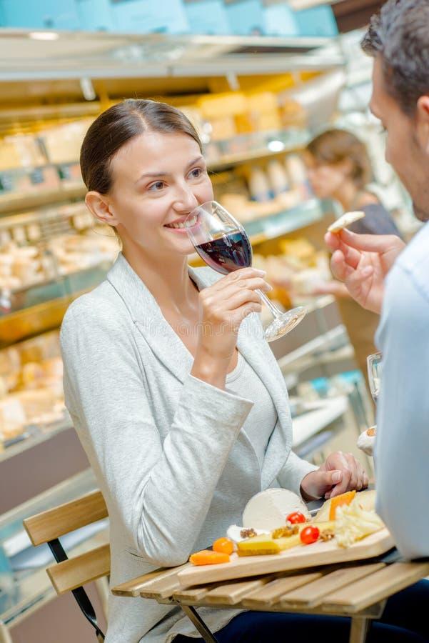 享用膳食饮用的酒的夫妇 图库摄影