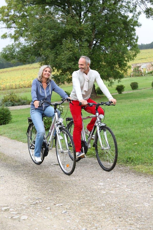 享用自行车的资深夫妇在晴天乘坐 免版税库存照片