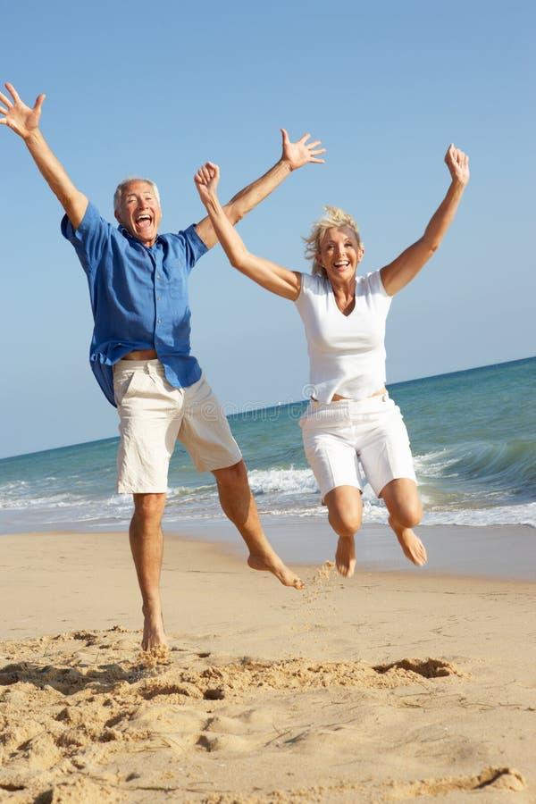 享用节假日前辈的海滩夫妇 免版税库存图片