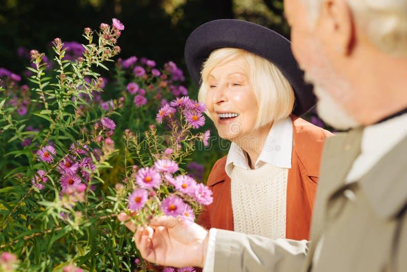 享用花的正面愉快的年迈的妇女嗅到 库存图片
