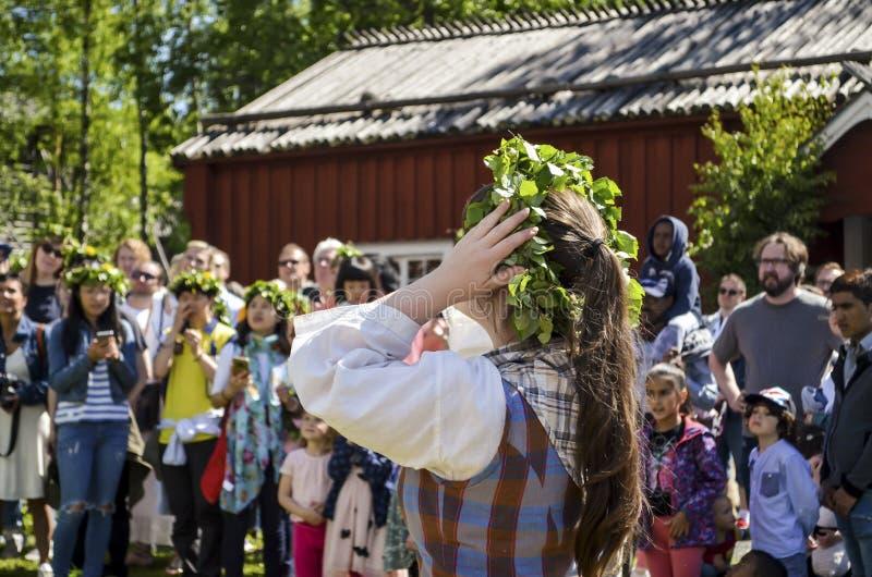 享用观看杆身分片刻和等待与五颜六色的愉快的妇女瑞典中间夏日庆祝 库存图片