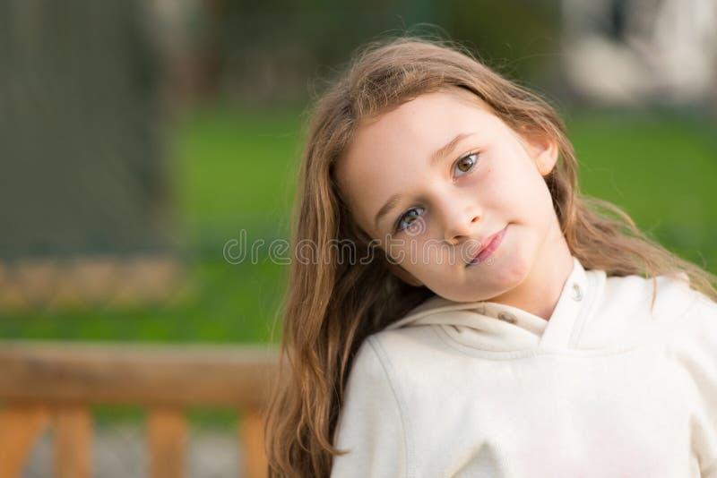享用逗人喜爱的白肤金发的女孩摆在和室外 库存照片