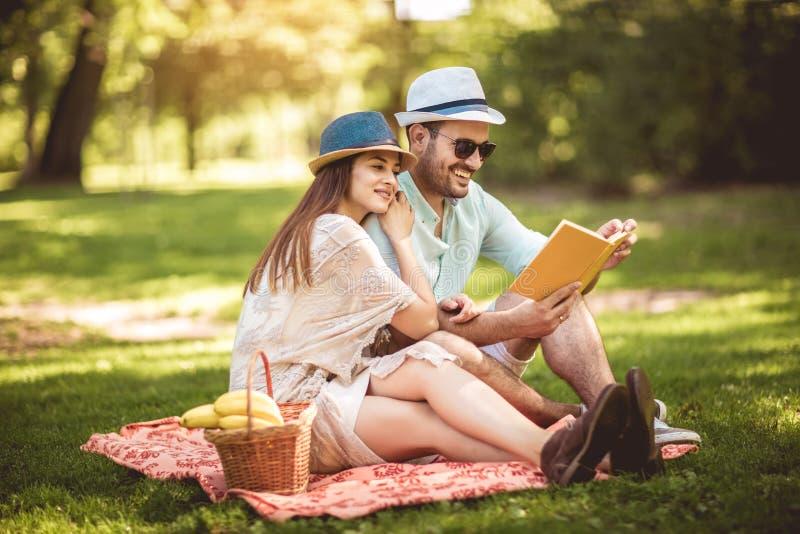 享用野餐时间室外阅读书的夫妇 图库摄影