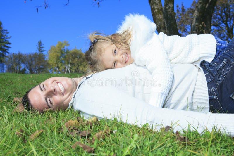 家庭成人_享用金黄叶子的家庭在秋天公园