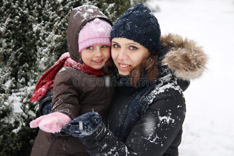 享用雪的母亲和女儿 库存照片