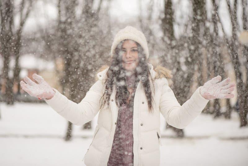 享用雪驱散它在空气、正面情感、喜悦和幸福的年轻美女 室外的冬天 免版税库存照片