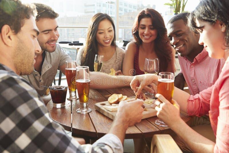 享用饮料和快餐在屋顶酒吧的小组朋友 免版税库存图片