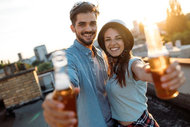 享用饮料和阳台的愉快的夫妇 免版税图库摄影